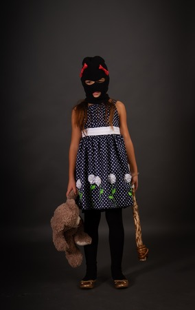 One teenage girl hooligans in bright smart dress, but in gangster balaclava hats with heavy clubs posing on a gray background with their favorite toy bear Фото со стока