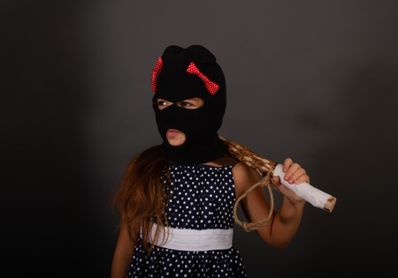 One teenage girl hooligans in bright smart dress, but in gangster balaclava hats with heavy clubs posing on a gray background
