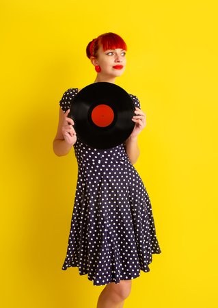 Pretty girl in retro dress in polka dot holding vinyl disc on a bright yellow background Stockfoto