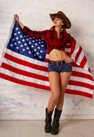 upright patriotic girl in a cowboy costume wearing a traditional wide-brimmed hat and shertach posing against a wooden background with the flag of the USA. Фото со стока