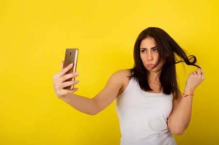 Young cute girl in casual clothes dabbles and grimaces and takes a selfie on her smartphone against a bright yellow background Standard-Bild - 118823536