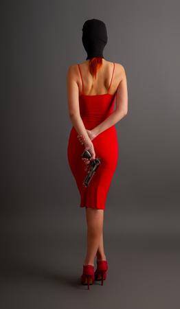 sexy girl in a tight red dress and balaclava holds an automatic pistol on her back against a dark background