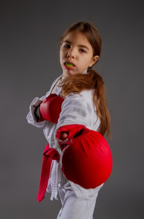 karate girl in kimono and red gloves for the fight with a protective mouthguard for a dark background Stock Photo