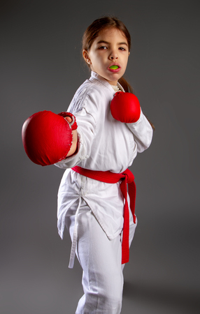 karate girl in kimono and red gloves for the fight with a protective mouthguard for a dark background 写真素材