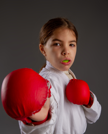 karate girl in kimono and red gloves for the fight with a protective mouthguard for a dark background Standard-Bild