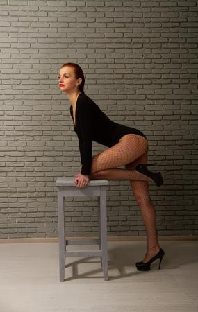 Giovane ragazza sensuale in costume da bagno nero e calze a rete e tacchi alti con uno sgabello alto grigio contro un muro di mattoni scuri
