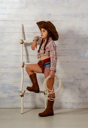 Niña con sombrero de vaquero de ala ancha y vestido tradicional con botas altas y con un lazo posando sobre un fondo de madera clara Foto de archivo