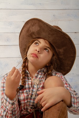 A little girl in a wide-brimmed cowboy hat wearing a traditional dress and high boots is eating a straw on a light wooden background