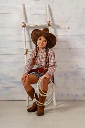 Little girl in a wide-brimmed cowboy hat and traditional dress in high boots and with a lasso posing on a light wooden background