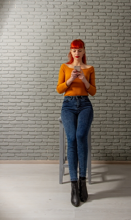 Young red-haired girl is reading something thoughtfully on her smartphone against a gray brick wall Stock Photo