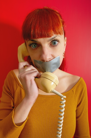 Conceptual picture. Young red-haired girl tries to talk on the phone with sealed with adhesive tape with her lips so that she keeps silence