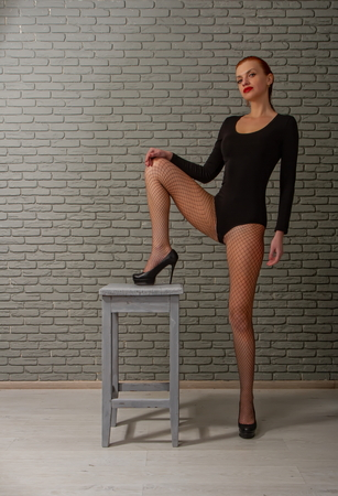 young girl with wet red hair in a black sports bodysuit and mesh pantyhose on a rough wooden stool against a gray brick wall