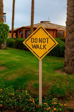 Yellow sign prohibiting walking Do not Walk on the green lawn of a tropical resort Stock Photo