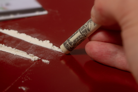 carta di plastica, cocaina versata in tracce e una banconota da un dollaro arrotolata in un tubo per prendere il farmaco su una superficie rosso scuro da vicino