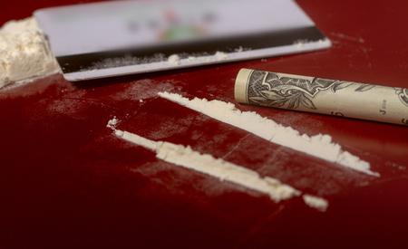 tarjeta de plástico, cocaína vertida en pistas y un billete de un dólar enrollado en un tubo para tomar la droga en un primer plano de la superficie de color rojo oscuro