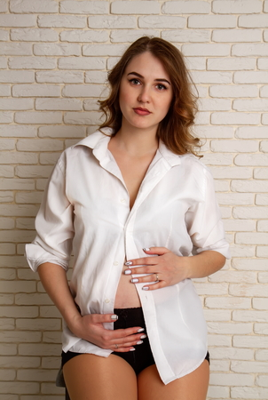 A beautiful young girl in her sixth month of pregnancy in a shirt of her husband and black dignified golf sits on a rough high stool against a brick wall.