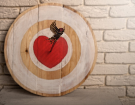 Handmade rough wooden target with a center in the form of a red heart and an arrow from a bow that hit the center