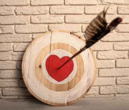 https://us.123rf.com/450wm/sharpner/sharpner1905/sharpner190500055/123353854-handmade-rough-wooden-target-with-a-center-in-the-form-of-a-red-heart-and-an-arrow-from-a-bow-that-h.jpg?ver=6