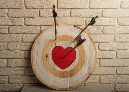 Handgefertigte raue Holzzielscheibe mit einem Zentrum in Form eines roten Herzens und einem Pfeil von einem Bogen, der die Mitte traf und zwei Pfeile verfehlt.