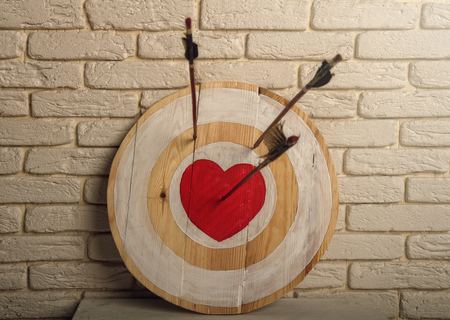 Handmade rough wooden target with a center in the form of a red heart and an arrow from a bow that hit the center and two arrows missed. Zdjęcie Seryjne - 123353855