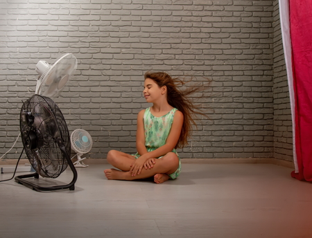 A little girl cools herself from the heat with the help of three different fans at once sitting on the floor of the room