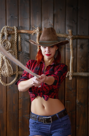 Young girl in traditional cowboy outfit in wide-brimmed hat and a plaid shirt throwing a lasso in a dark room