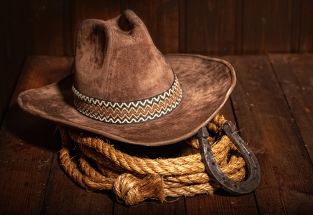 An old horseshoe lies next to a classic cowboy hat and lasso on a dark wooden background.