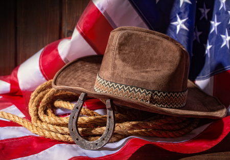 Classic cowboy hat lasso and horseshoe lie on a star-striped USA flag on a dark wooden background
