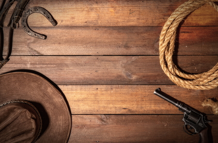 Old classic wooden background from the symphols of the cowboy wild west. Lasso, hat, revolver and horseshoe with space for text