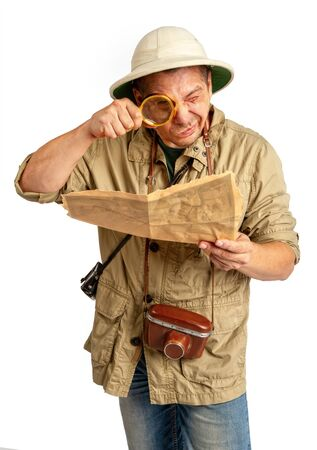 Adult tourist in tropical pith helmet and protective clothing looks into a magnifying glass on an old map.