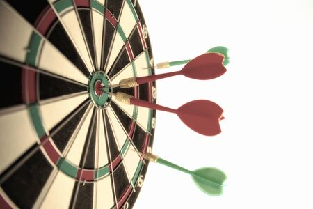 Close-up dart board with a red arrows that hit the center of the target