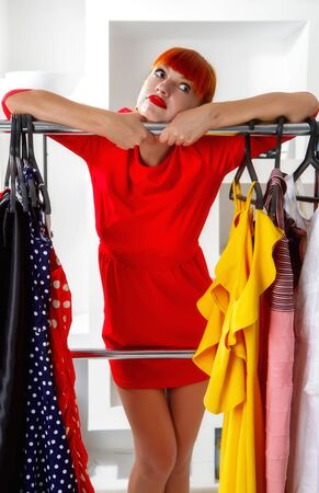 A young girl chooses in a wardrobe on a hanger what dress to wear