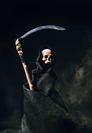 conventional death symbol with a slanting skull in a dark robe with a hood on a dark background