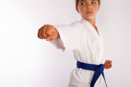 karate girl in white kimono and blue belt punch forward Stock Photo