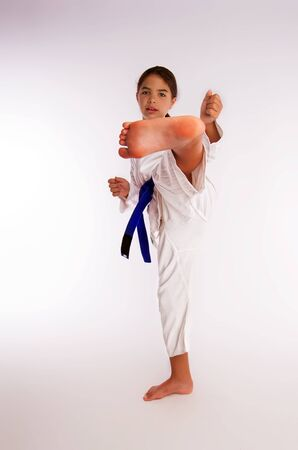 karate girl in white kimono and blue belt kicks