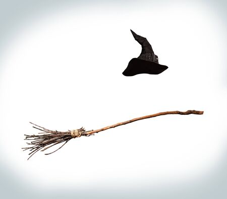 classic pointed witch hat and flying broom flying on a white background 版權商用圖片