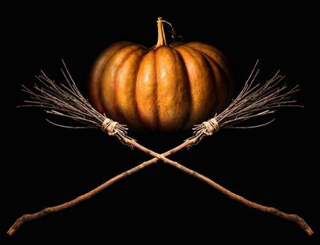 big orange pumpkin and two witches classic crossed brooms on a dark background