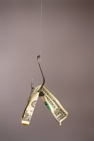Conceptual image of a fish hook with a dollar banknote suspended from it for bait. Banque d'images