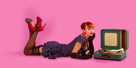 Pin-up model girl in retro polka-dot dress listens to an old gramophone on a pink background Stockfoto
