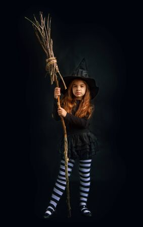 little witch girl in traditional Halloween dress and pointed hat is standing with a wooden whisk on a dark background 写真素材