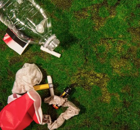 empty bottles of batteries and other household rubbish thrown out by unconscious people onto green grass in nature