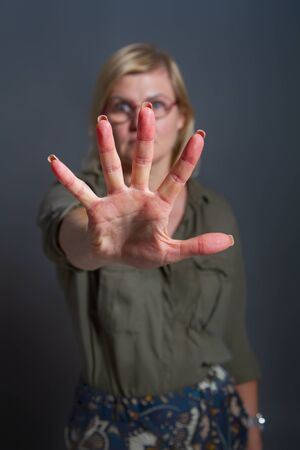 Adult woman shows stopping or prohibiting gesture with hand