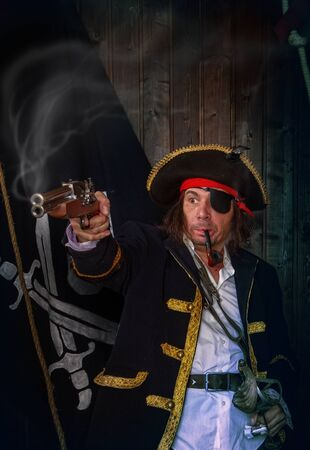 Adult pirate captain in a traditional costume shoots a pistol and holds a sword in his hands against the background of a jolly roger 版權商用圖片