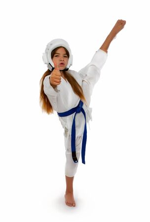karate girl in a protective helmet with a blue belt and a white kimono with a capa in her lips smiling shows her thumb that everything is fine. Stok Fotoğraf