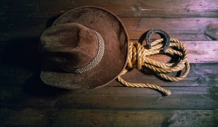 steel classic horseshoe cowboy hat and coarse rope on a dark wooden background top view