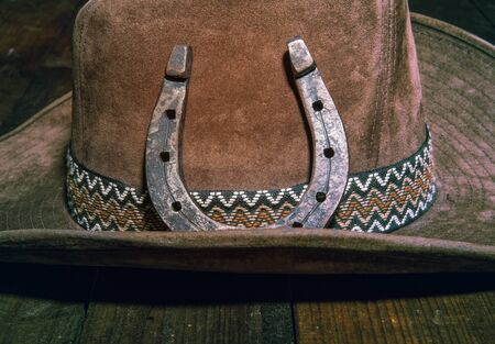 steel classic horseshoe lying on a brown cowboy hat close-up