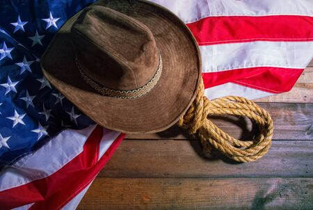 brown classic cowboy hat, coarse rope and big american flag lying on dark boards