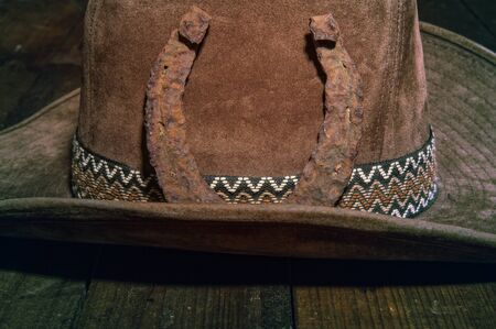 very old and rusty steel classic horseshoe lying on a brown cowboy hat