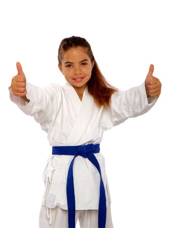 little karate girl in a white kimono and a blue belt shows a sign perfectly holding thumb up