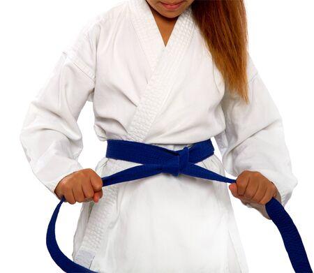 little karate girl in a white kimono ties a new blue belt
